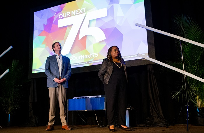 Jeff Broadhurst of Eat and Park and Toni Murphy of Comcast stand on stage during the Our Next 75 Summit on July 27